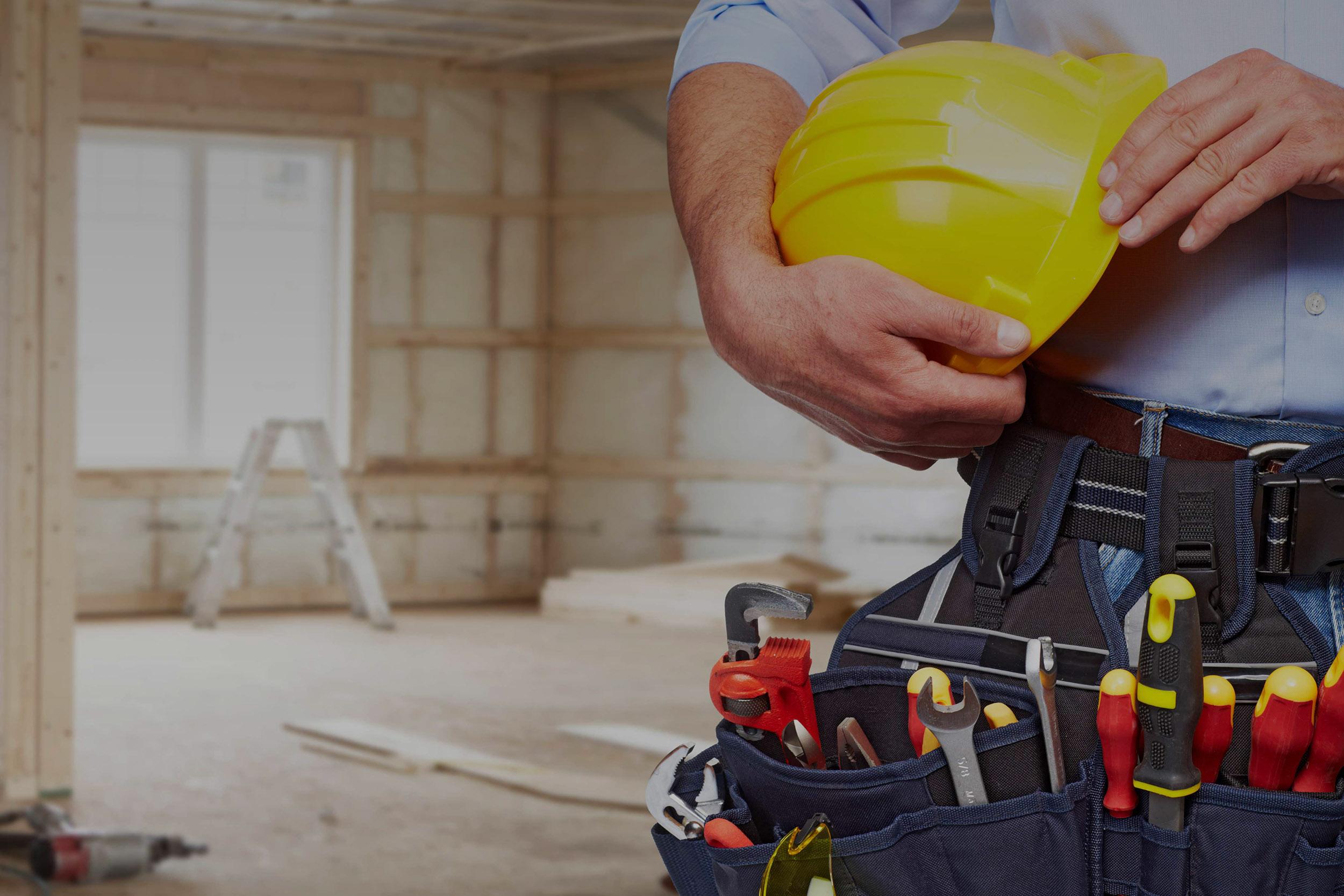 Chlap držící přilbu na stavbě